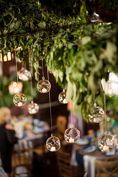 glass orbs with votive candles suspended from a canopy of greenery