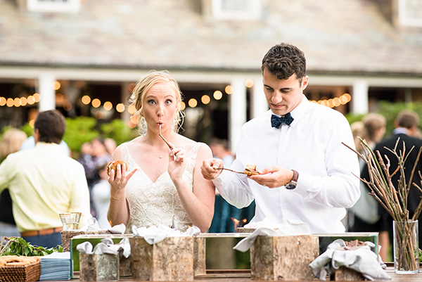 bride and groom roasting marshmallows at a s'mores bar