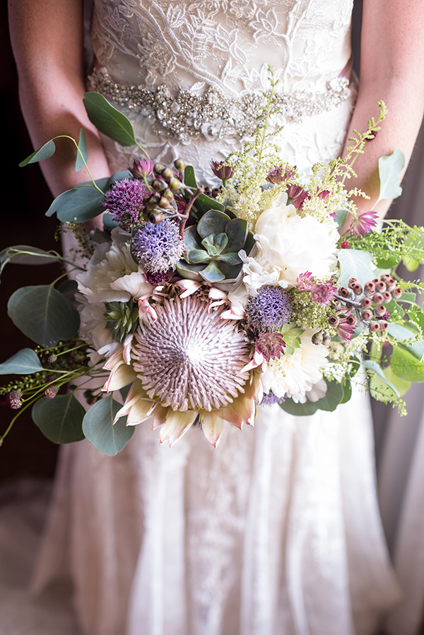 bride holding a boho wedding bouquet featuring protea and succulents