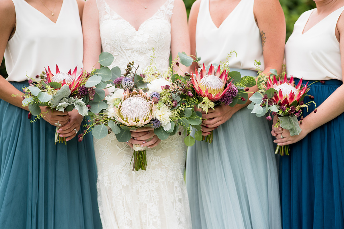 bride and bridesmaids holding boho wedding bouquets featuring protea and succulents