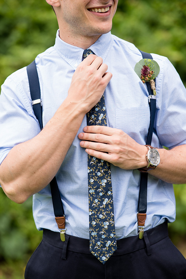 groomsman wearing a pale blue shirt with navy blue patterned tie, suspenders, and a boutonniere