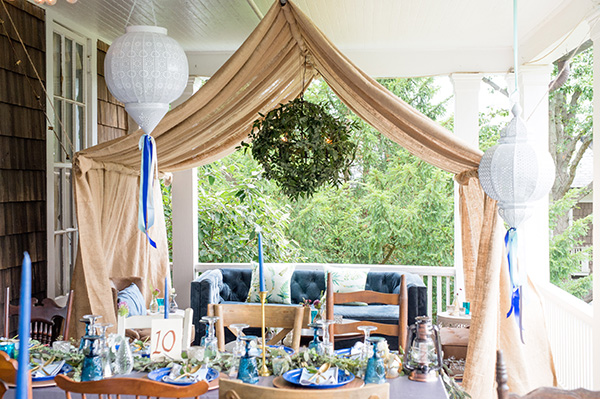 wedding reception table with cozy seating area under a canvas tent