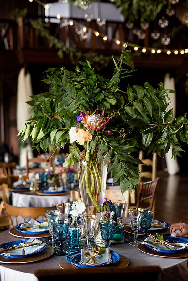 tall floral centerpiece featuring protea and greenery