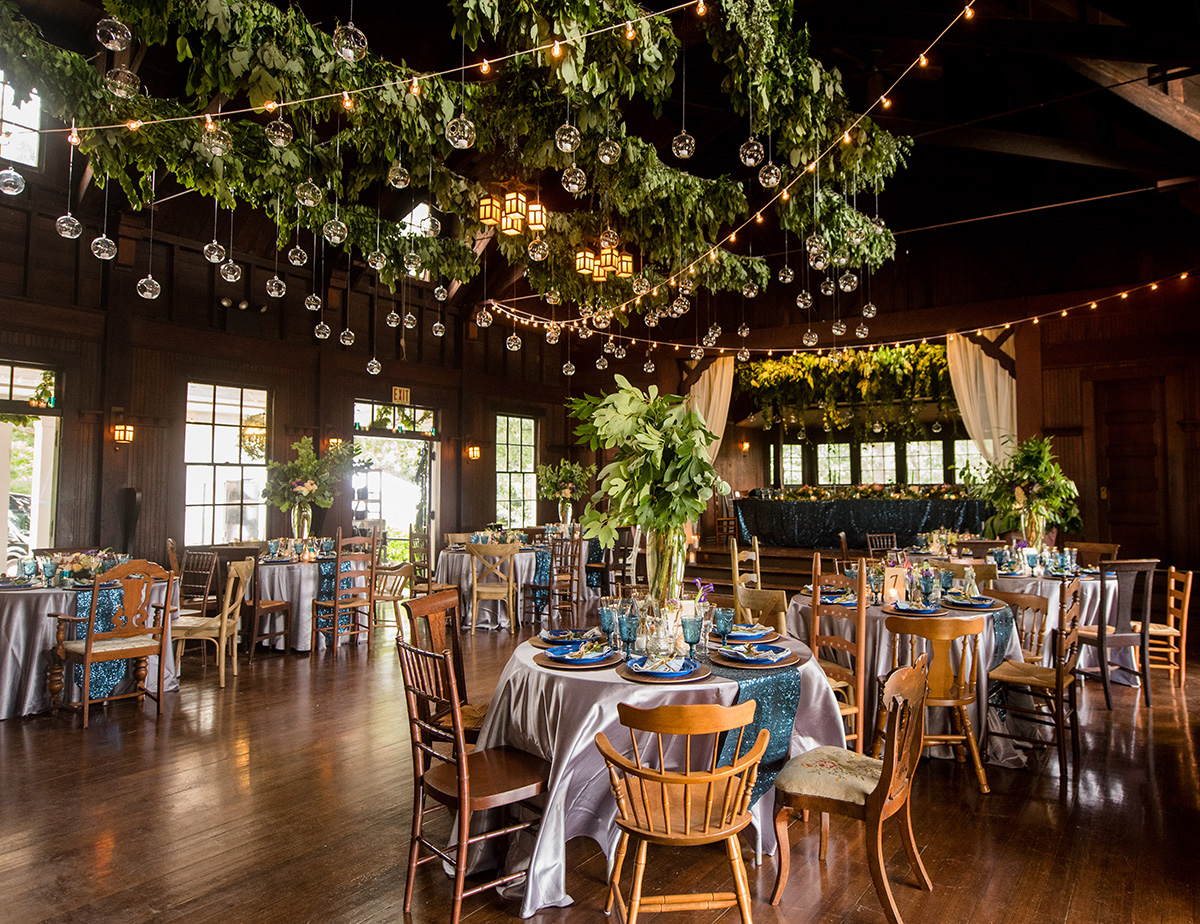 round tables set up for a wedding reception with greenery garlands, twinkle lights, and blue accents