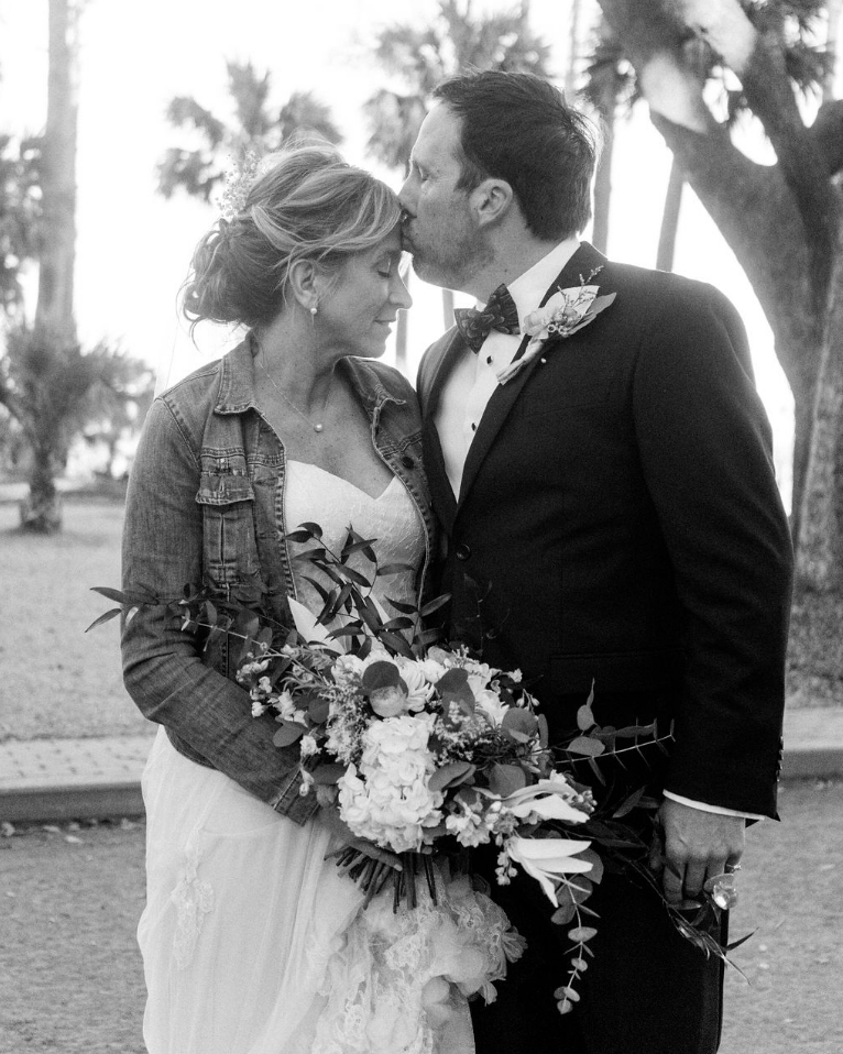 black and white photo of a groom kissing his bride on the forehead