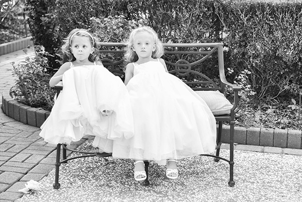 black and white photo of two flower girls in white dresses sitting on a bench