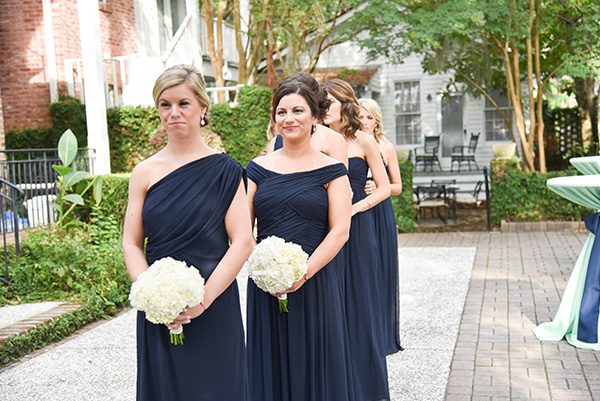 bridesmaids lined up ready to walk down the aisle wearing navy blue dresses and carrying white hydrangea bouquets