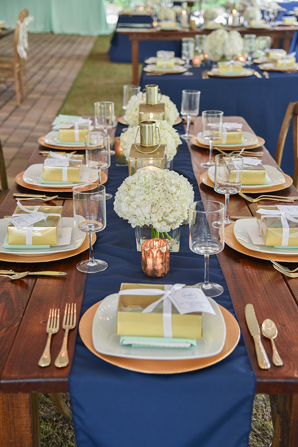 table setting with navy blue table runner, gold charger and flatware, with a gift box on each plate