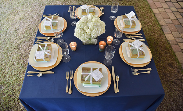 square table with a navy blue tablecloth viewed from above with six table settings
