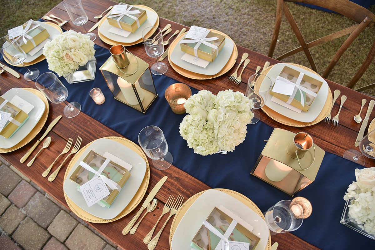 Wedding reception table shown from above with navy blue runner, gold decor accents and hydrangea bouquets