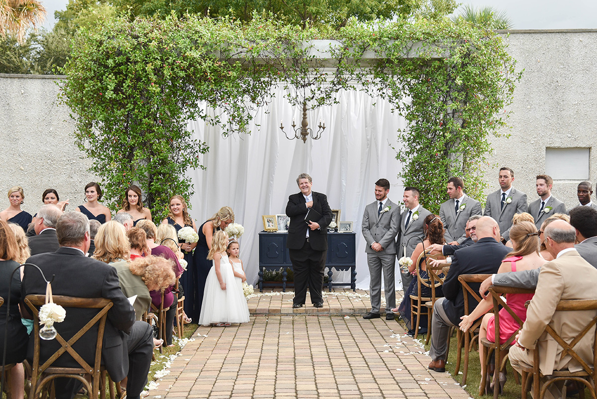 outdoor wedding ceremony with a vine-covered arbor as the altar