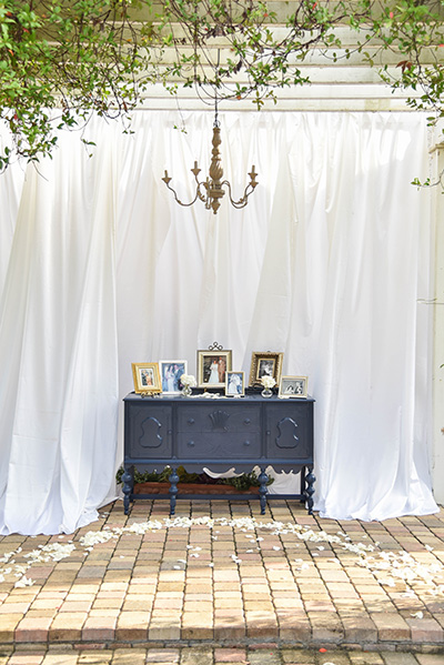 buffet table with family photos in picture frames set against a white curtain