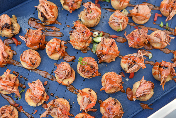 BBQ pulled pork and shrimp appetizers on a navy blue tray