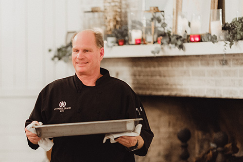 Chef Christopher Hewitt carrying a tray of food