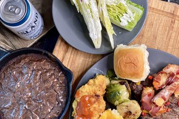 Hearty meal with salad, beer, and a brownie in a cast iron skillet