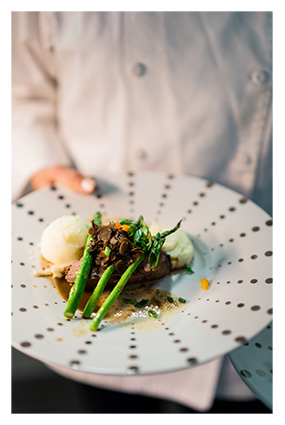 server in a white coat holding a plate with a catered meal of beef in a mushroom demi, asparagus, and mashed potatoes