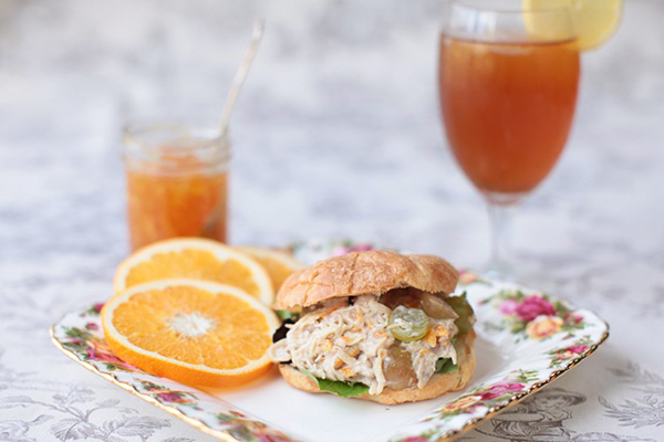 chicken salad sandwich made with a croissant alongside a glass of sweet tea