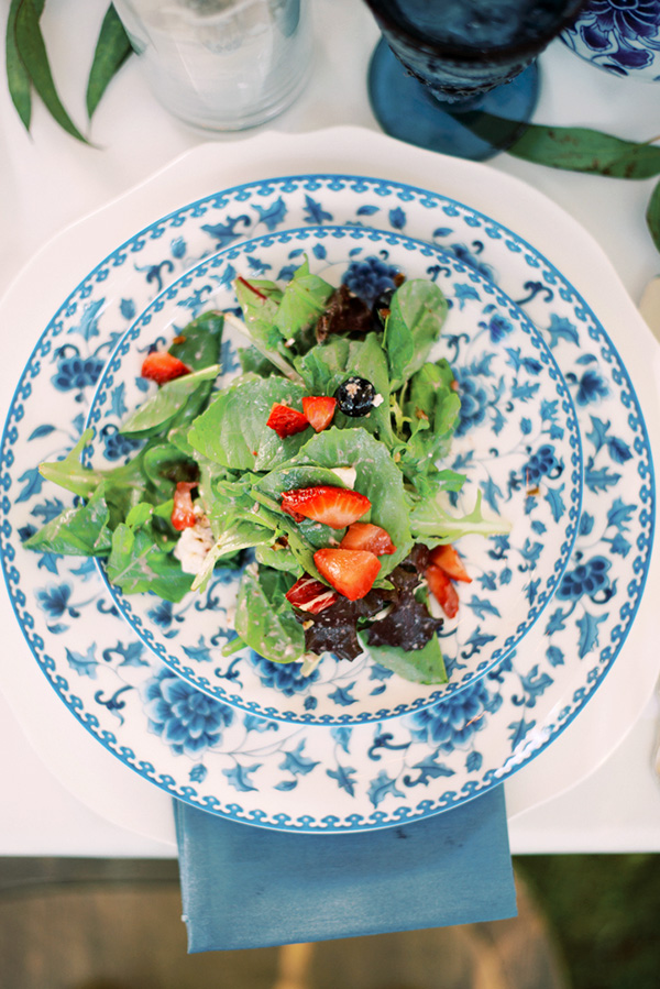 fresh greens and strawberries on blue patterned china