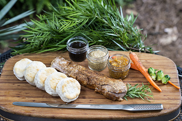 pork tenderloin and biscuits on a cutting board with various spreads in small glass jars