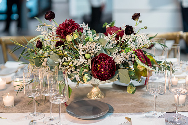 Floral centerpiece with red and white flowers in a mercury glass vessel