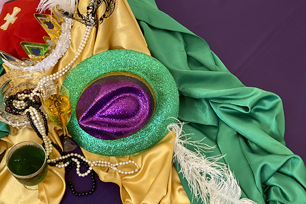 purple, green, and yellow mardi gras beads and hats