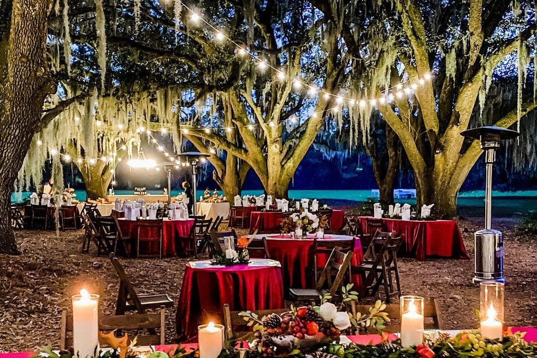 tables set under a canopy of live oaks and lit by glowing cafe lights and candles